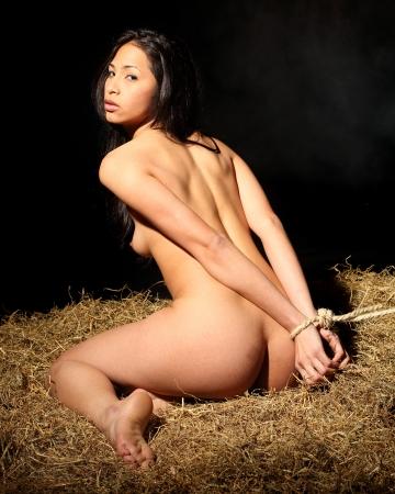 mujeres negras desnudas: estilo bondage con una hermosa mujer desnuda que est� atado con una cuerda y que se sienta en un calabozo Foto de archivo