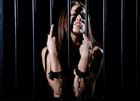 very sexy and beautiful woman locked behind black prison bars  Stock Photo - 18353439