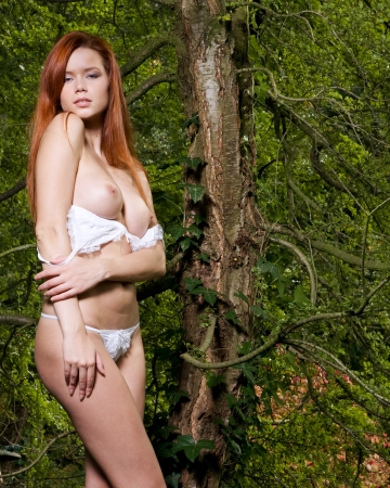 natural looking woman in lingerie with red hair is posing outside in the nature Stock Photo - 18569239