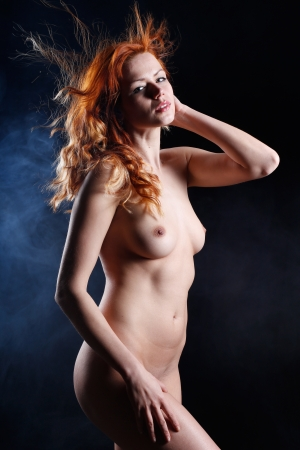 very sexy and beautiful nude or naked woman with red hair on a black background with smoke