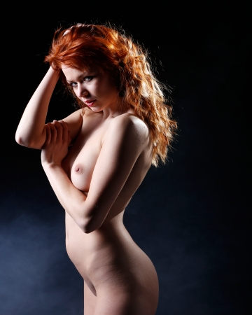 very sexy and beautiful nude woman with red hair on a black background with smoke Stock Photo - 18660593