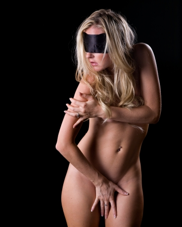 erotic fantasy: sexy nude  woman with silk blindfold on a dark background