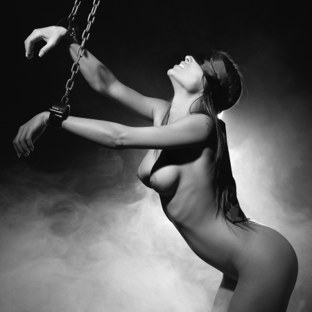 very sexy nude or naked woman bound in bondage fifty shades of grey style with medieval iron shackles or cuffs and she is blindfolded with a silk blindfold and behind her smoke and lights