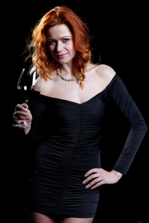 czech women: very sexy woman with beautiful red hair in a dark cocktail dress is drinking a glass of red wine and behind her a dark background Stock Photo