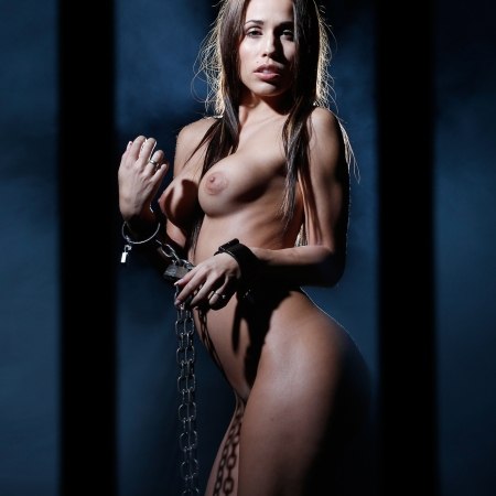 bondage art style with nude woman tied up with a chain and cuffs and locked behind prison bars Stock Photo