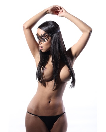 super sexy and very beautiful half naked top model with a venetian mask on her face and black stockings on her legs photo