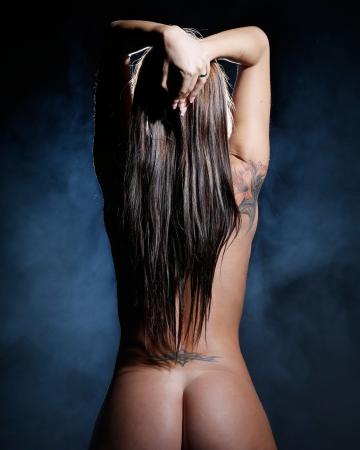naakt: zeer sexy en mooie naakt of naakt vrouw met bruin donker haar is bedekt met rook en licht
