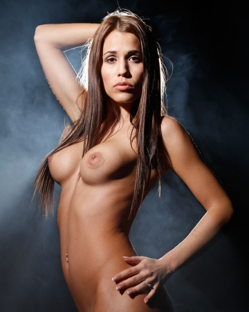 very sexy and beautiful nude woman with brown dark hair is covered with smoke and light