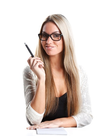 sexy teacher: a very beautiful business woman or secretary is working in her office and she is sitting behind a  white desk with pen and paper
