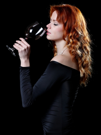 very sexy woman with beautiful red hair in a dark cocktail dress is drinking a glass of red wine and behind her a dark background photo