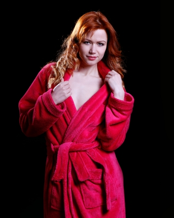 very beautiful and sexy woman with flaming red hair is dressed only in a bathrobe photo