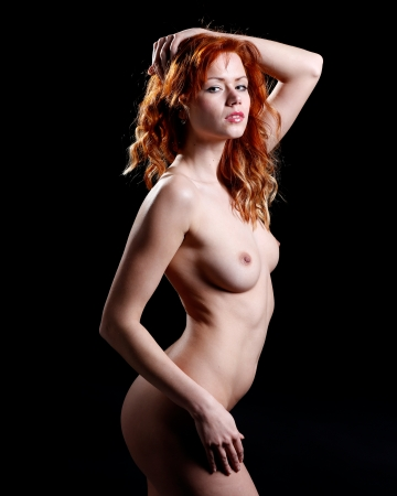 very sexy and beautiful nude woman with red hair on a black background