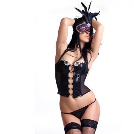 ropa interior femenina: hermosa mujer g�tica sexy o lencer�a negro rizado con un misterioso veneciano m�scara que cubre su cara hecha en el estudio sobre un fondo blanco