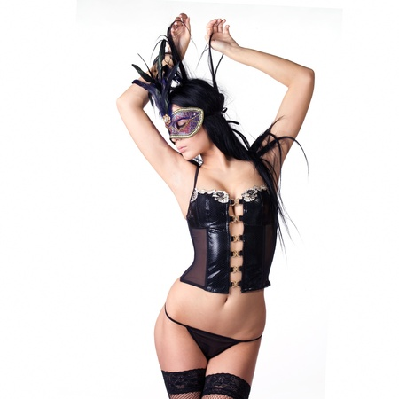 kinky: beautiful woman in sexy gothic or kinky black lingerie with a mysterious venetian facemask covering her face made in studio on a white background
