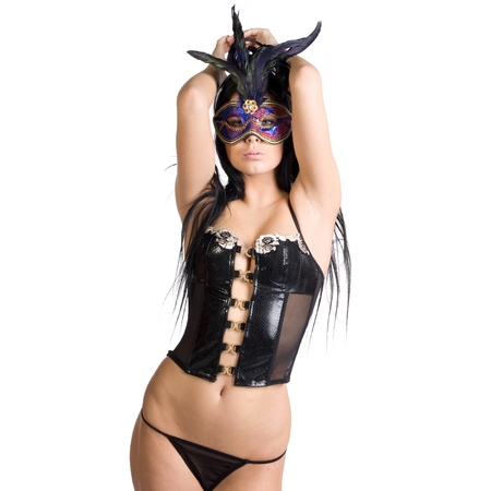 masque: beautiful woman in sexy gothic or kinky black lingerie with a mysterious venetian facemask covering her face made in studio on a white background