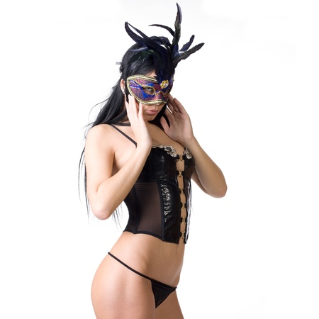 beautiful woman in sexy gothic or kinky black lingerie with a mysterious venetian facemask covering her face made in studio on a white background