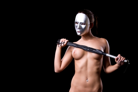 beautiful nude or naked woman witha kinky venetian mask covering her face is holding a whip in her hands and image made on a black background photo