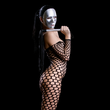 beautiful nude or naked woman dressed only in fishnet stocking or dress and she is holding a whip in her hands and her face is covered with a kinky scary mask or facemask on a dark black background photo