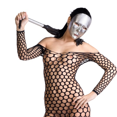 beautiful nude or naked woman dressed only in fishnet stocking or dress and she is holding a whip in her hands and her face is covered with a kinky scary mask or facemask on a white background photo