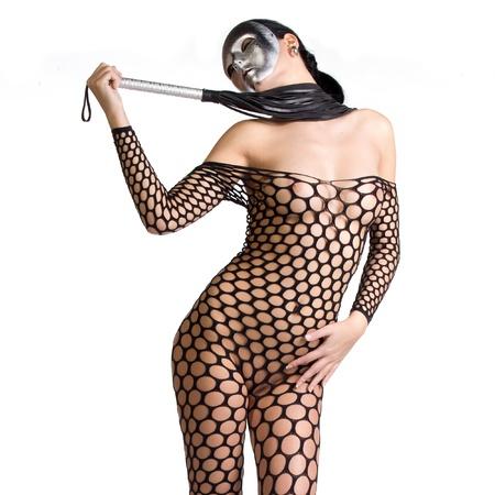 ragazza nuda: bella nuda o donna nuda vestita solo di calze a rete o vestito e lei � in possesso di una frusta in mano e il volto � coperto da una maschera di paura viziosa o maschera su uno sfondo bianco