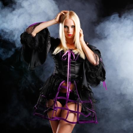 maquillaje de fantasia: sexy rubia mujer vestida en estilo gótico de Halloween o con el fondo oscuro humo