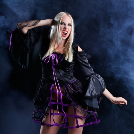 sexy blonde woman dressed in halloween or gothic style with dark smoke background photo