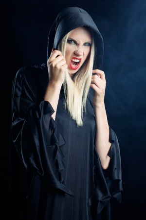 sexy blonde woman dressed in a dark cape in halloween or gothic style with dark smoke background photo