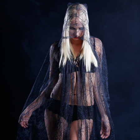 sexy blonde woman dressed in a lace shine dress in halloween or gothic style with dark smoke background photo