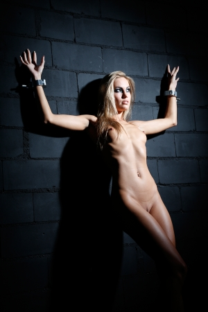 bondage art style with beautiful nude or naked caucasian white blonde woman tied up with a heavy steel or iron cuffs or handcuffs against a dark brick dungeon wall