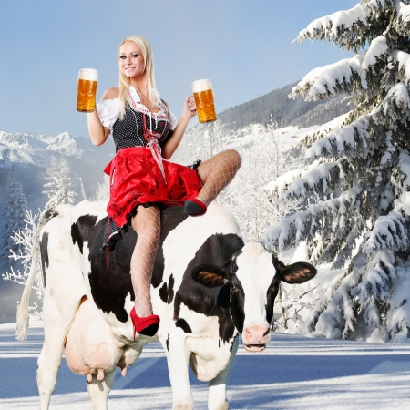 crazy oktoberfest or tiroler creation with a very beautiful woman who is sitting on a cow and serving beer and in the background snow and mountains photo