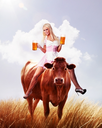 crazy oktoberfest or tiroler creation with a very beautiful woman is sitting on a cow and serving beer photo