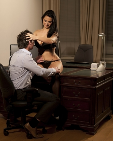 Very beautiful and sexy woman in lingerie is sitting on a desk and is working late with her manager at the office photo