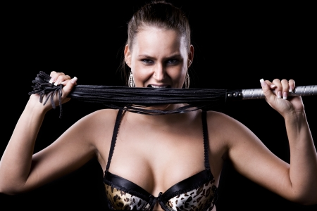 beautiful woman is holding a whip between her teeth photo