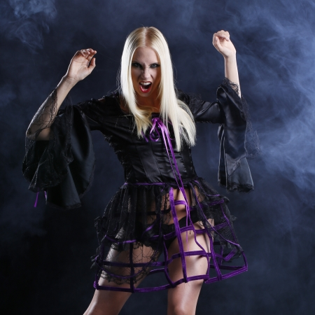 gothic woman: sexy blonde woman dressed in halloween or gothic style with dark smoke background Stock Photo
