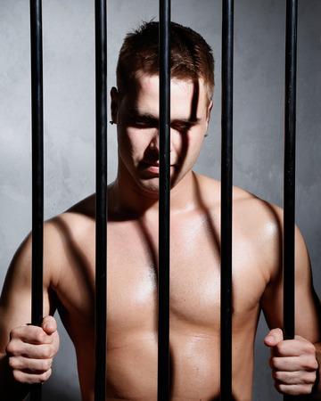 affraid: Sexy man behind iron prison bars