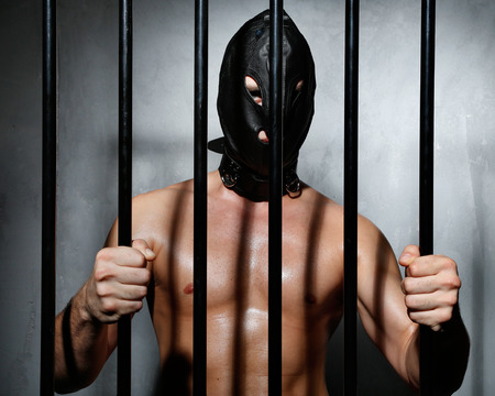 jail background: Sexy man behind iron prison bars with leather mask