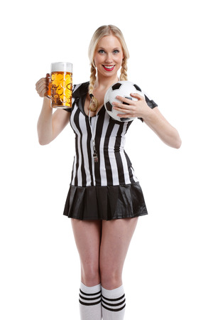 very happy and sexy beautiful woman in soccer referee clothes with a big glass of beer and a ball in her hands ready to party photo