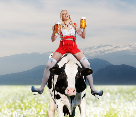 beautiful and sexy woman in tiroler or oktoberfest dirndl or dress is sitting on a cow and having a big glass of beer in her hands photo