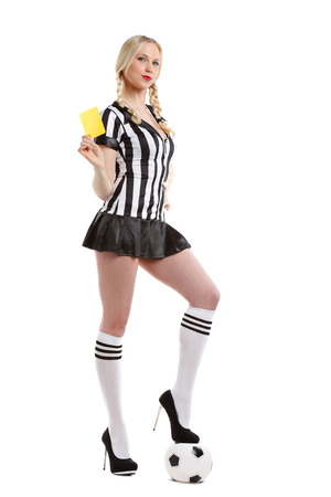 beautiful and sexy woman in soccer referee playing shirt is holding her yellow card up and one foot on a ball photo