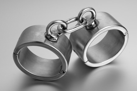 cuffs: closeup of hard steel handcuffs or cuffs Stock Photo