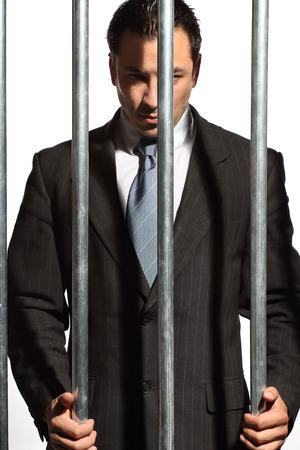 prison bars: very good looking man dressed in a nice suit behind prison bars