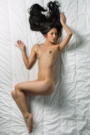 Beautiful nude woman is laying on a bed photo