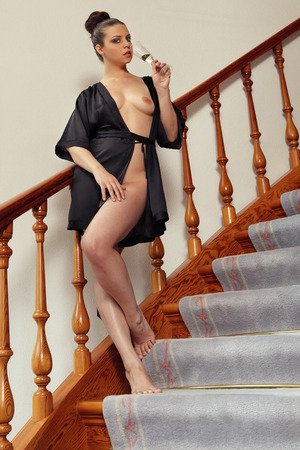 sexy nude women: Beautiful woman is drinking a glass of wine standing on the stairs
