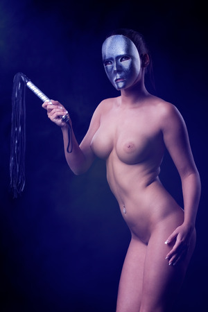 Beautiful nude woman is holding a whip in her hands and on the background blue light and smoke photo