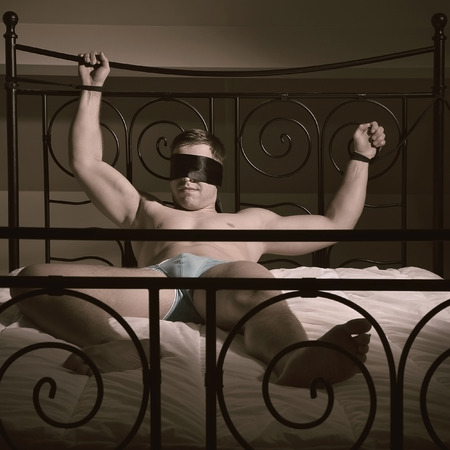 Man laying in a bed and his hands are tiedup and he is blindfolded Foto de archivo