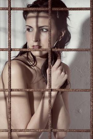 kinky: Very Beautiful woman posing in an iron cage Stock Photo