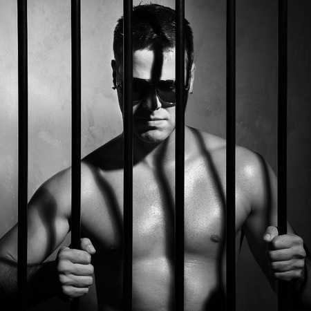 Sexy muscular man behind prison jail bars Stock Photo