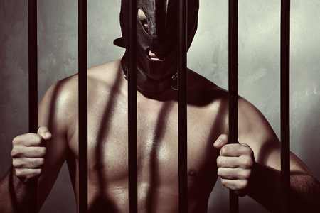 Big muscular man behind prison jail bars and he is wearing a leather mask