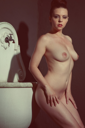 Beautiful naked woman is posing against an old sink and image in vintage tone