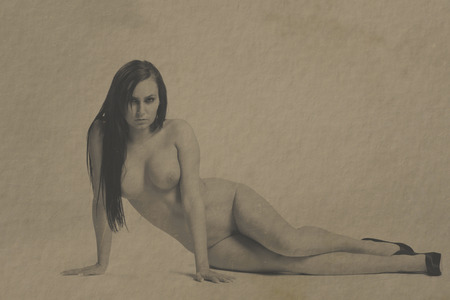 Beautiful nude woman and image given an old brown vintage paper look with dust and scratches Stock Photo